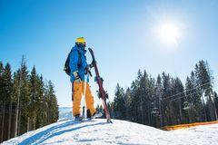Skier in the mountains. Full length shot of a skier standing on top of a snowy slope in the mountains looking around enjoying beautiful sunny winter day. Winter Stock Photo