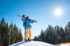 Skier in the mountains. Full length shot of a skier standing on top of a snowy slope in the mountains, raising his arms in the air, enjoying beautiful sunny Stock Image