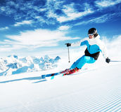 Skier in mountains, prepared piste and sunny day royalty free stock image