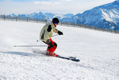 Skier moving down a ski track. Male skier skiing down a ski track, mountains at a background Royalty Free Stock Photography