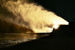 Skier near a snow cannon making powder snow. Alps ski resort. Royalty Free Stock Images
