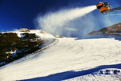 Skier near a snow cannon making powder snow. Alps ski resort. Stock Photo