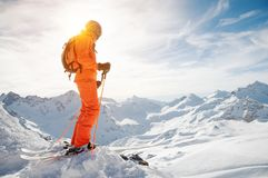 A skier in an orange overall with a backpack on his back wearing a helmet and with ski poles in his hands is standing on Stock Photo