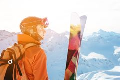 A skier in an orange overall with a backpack on his back wearing a helmet and with ski poles in his hands is standing on. A precipice in front of a snowy abyss Royalty Free Stock Photography
