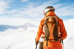 A skier in an orange overall with a backpack on his back wearing a helmet and with ski poles in his hands is standing on Royalty Free Stock Images