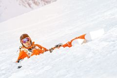 A skier in an orange overall and with a backpack lies happy in the snow after falling. The concept of recreation in the mountains and skiing Stock Photos