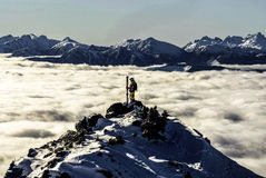 Skier on a peak. A female skier on top of a peak surrounded by a sea of clouds. Coast Mountains, British Columbia, Canada stock images