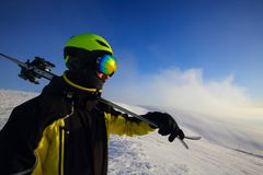 Skier on a peak. Skier holding a pair of skis looking at the mountains royalty free stock photos