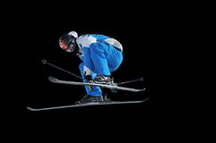 Skier performing a high jump. Skier in blue and white performing a high jump, while touching his skis with his hands on black background Stock Image