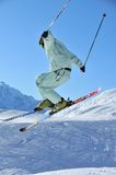 Skier performing a jump. A skier in pale green clothing performing a jump with mountains in the background Stock Image