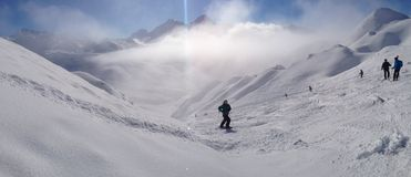 A skier on the piste in front of beautiful mountains Stock Image
