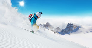 Skier on piste running downhill Stock Image