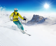 Skier on piste running downhill Royalty Free Stock Image