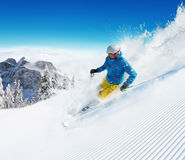 Skier on piste running downhill Stock Photo