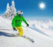 Skier on piste running downhill Stock Image