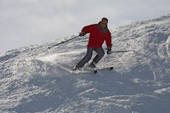 Skier in red. The mountain skier in red goes down on snow mountain Royalty Free Stock Image