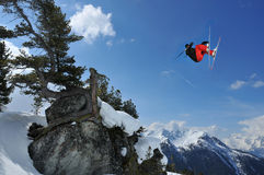 Skier in red and black performs high jump. A skier performing a high jump over a rock with a gnarled pine. In the background snow covered mountains Royalty Free Stock Photos