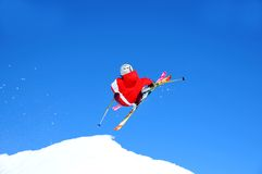 Skier in red taking off on a jump Royalty Free Stock Images