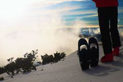 Skier in red winter jacket with  fun snowshoes stay in snow in mountains. Fogy winter day at peak Royalty Free Stock Photography