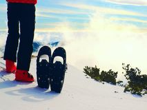 Skier in red winter jacket with  fun snowshoes stay in snow in mountains. Fogy winter day at peak Stock Photo