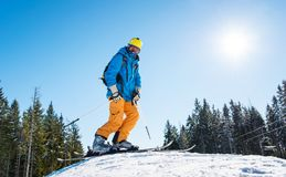 Skier resting on top of the mountain. Low angle and full length shot of a skier with riding equipment standing on top of the hill in the mountains at ski resort Royalty Free Stock Photos