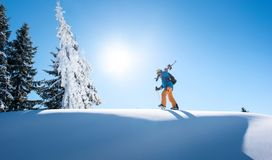 Skier resting on top of the mountain. Male skier walking on top of the mountain with his skis on his shoulder on a sunny winter day sunlight nature recreation Stock Photo