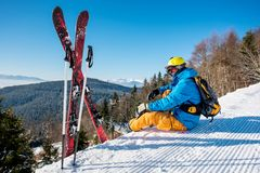 Skier resting on top of the mountain. Professional skier sitting on top of the mountain near his skiing equipment relaxing enjoying beautiful snowy mountains Royalty Free Stock Image