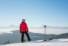 Skier resting on top of the mountain. Rearview shot of a skier resting after the ride standing on top of the ski slope looking around enjoying breathtaking view Stock Images