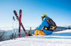Skier resting on top of the mountain. Rearview shot of a skier sitting on top of the mountain near his skiing equipment relaxing enjoying beautiful snowy Royalty Free Stock Photo