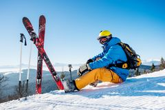 Skier resting on top of the mountain. Shot of a professional skier sitting on top of the mountain near his skiing equipment relaxing enjoying beautiful snowy Stock Photo