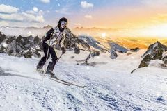Skier rides downhill in rocky mountains ski resort Royalty Free Stock Photo
