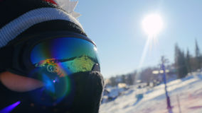 Skier rides in glasses lift chairs on sunny winter day up the beautiful mountains with lense flare effects Stock Photography
