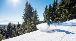 Skier riding in the mountains on a sunny winter day. Skier riding downhill in the mountains copyspace sports recreation winter ski resort people lifestyle active Royalty Free Stock Photography