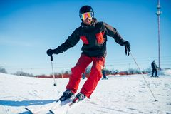Skier riding from speed slope, front view. Skier in helmet and glasses riding from speed slope, front view. Winter active sport, extreme lifestyle. Downhill Stock Photos