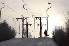A skier rises on a ski lift on a snow-covered hill against the backdrop of bright sun. Work lifts in the winter. Ski resort and stock photos