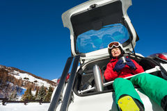 Skier sitting in car boot and drinking warm tea Stock Photography