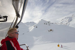 Skier sitting in chair lift Stock Photography