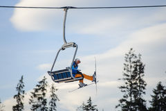 Skier sitting at ski lift against blue sky Stock Image