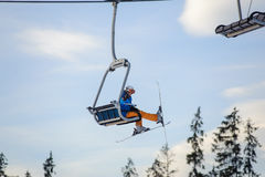 Skier sitting at ski lift against blue sky Stock Photos