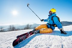 Skier resting on top of the mountain. Skier sitting on the ski slope taking a selfie using selfie-stick resting relaxing extreme recreation lifestyle activity Royalty Free Stock Photos