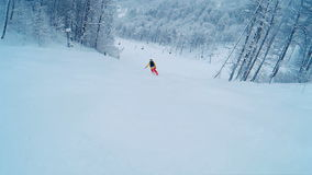 Skier skiing down the groomed slopes of mountain in the evening. First-person view stock footage