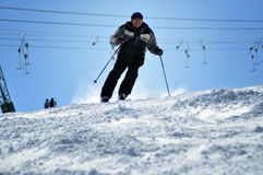 Skier skiing down the slope in a beautiful sunny day Stock Images