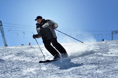 Skier skiing down the slope in a beautiful sunny day Royalty Free Stock Images
