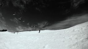 Skier skiing down on the slope. Black and white HD movie Stock Images