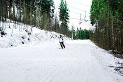 Skier is skiing down the slope in the woods. In winter Royalty Free Stock Photo