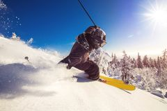Free Skier Skiing Downhill During Sunny Day Fresh Snow Freeride. Extreme High Speed, Frosty Dust Scatters Royalty Free Stock Photography - 161646367