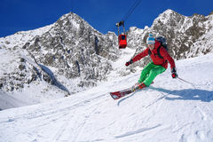 Skier skiing downhill in high mountains against cable lift Royalty Free Stock Photography