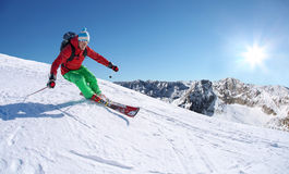 Skier skiing downhill in high mountains against cable lift Royalty Free Stock Image