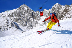 Skier skiing downhill in high mountains against cable lift Stock Photo
