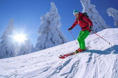 Skier skiing downhill in high mountains against sunset Royalty Free Stock Image